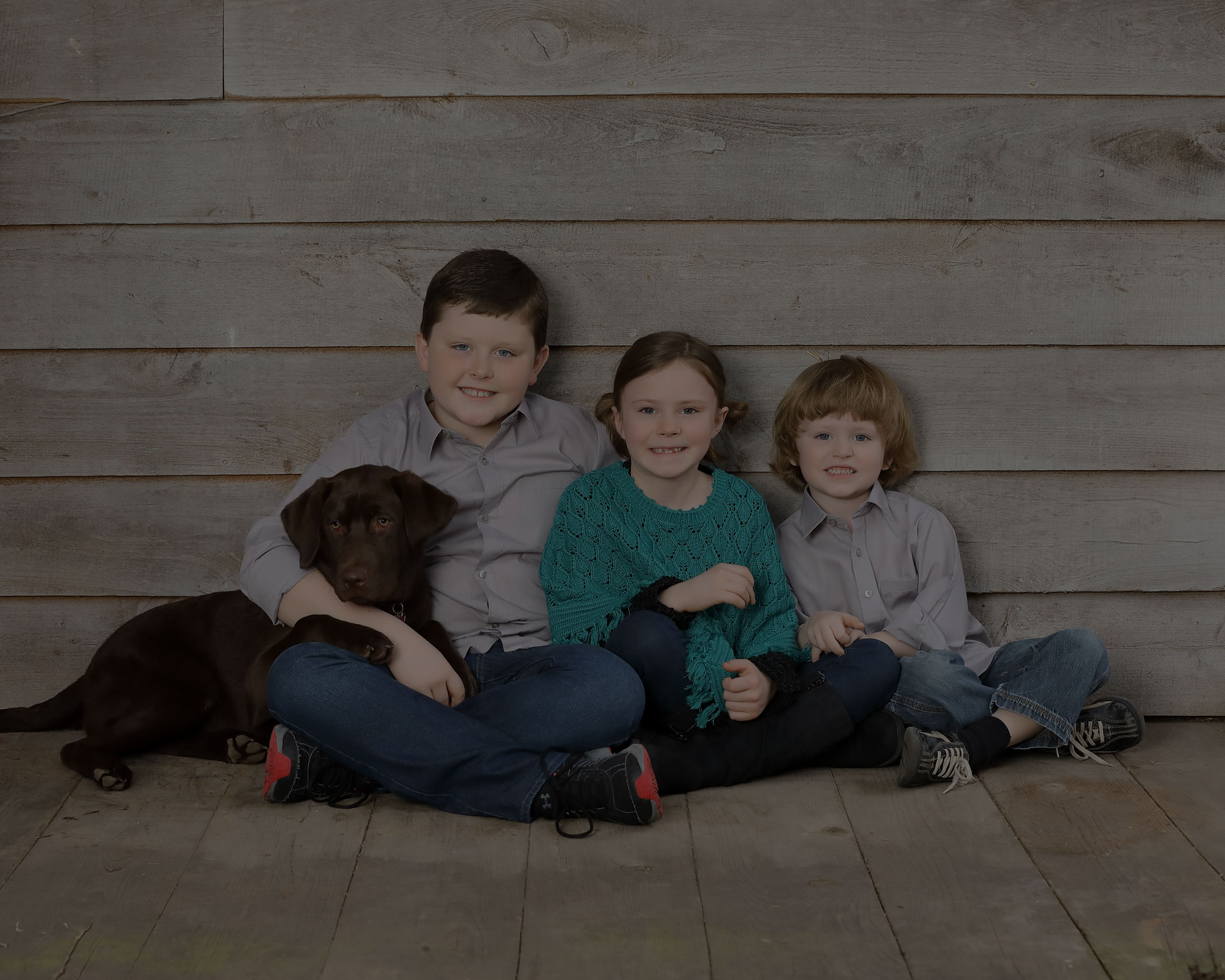 3 children siting on the wooden floor with a chocolate color Labrador dog