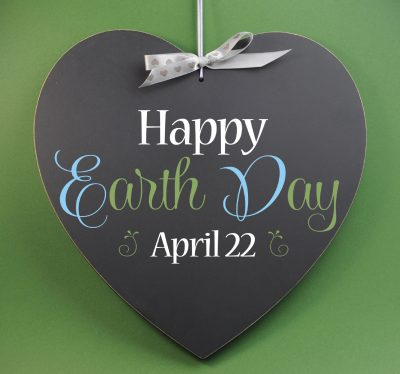 Happy Earth Day April 22, message sign greeting on a heart shaped blackboard against a green background.